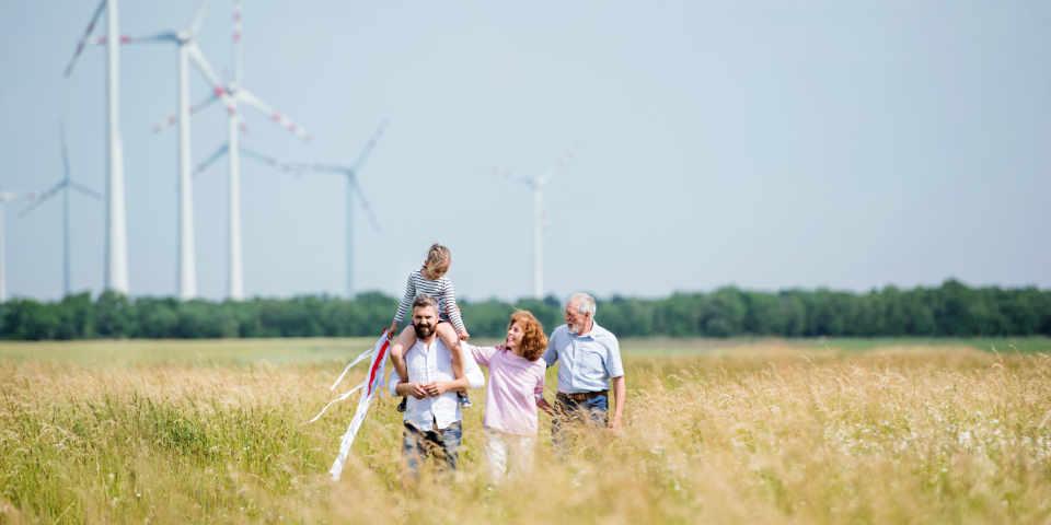 Familie geht auf einem Feld spazieren, im Hintergrund sind Windräder zu sehen
