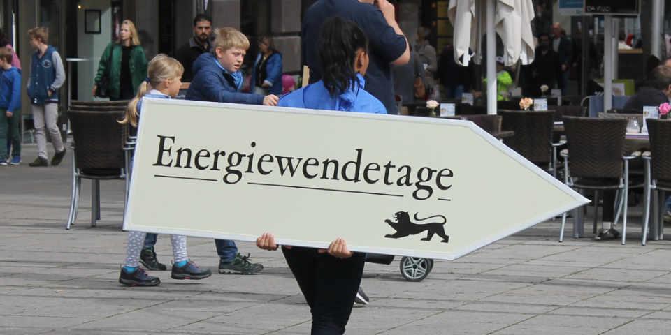 Frau weist mit Schild auf Energiewendetage hin