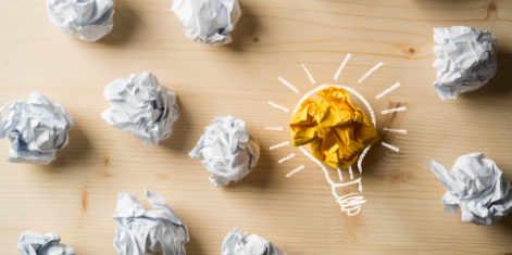 Papierkugeln als Symbol für Ideen mit Glühbirne